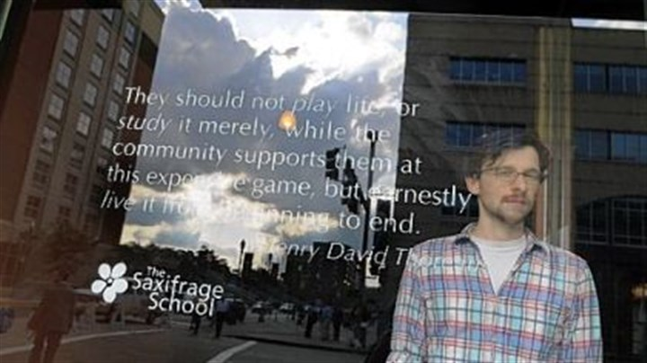 The Saxifrage School Tim Cook, founder of The Saxifrage School, stands by a quote by Henry David Thoreau on a window at the organization's office on the North Side.