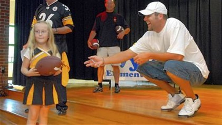 The winner Wyland kindergartener Jessica Leventry receives an autographed football from Ben Roethlisberger. Jessica, won a raffle for the ball.