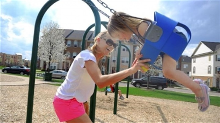 Towns 2 Natalie Bollinger pushes daughter Livi on the swing at the park in the Village at Pine.