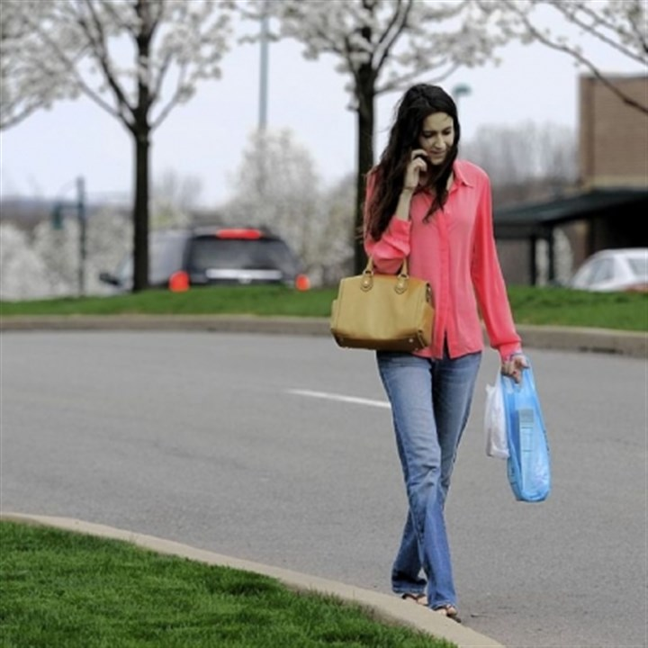 Towns 5 Elizabeth Ascencio walks home along Village Run Drive after making a quick stop at Giant Eagle in Pine.