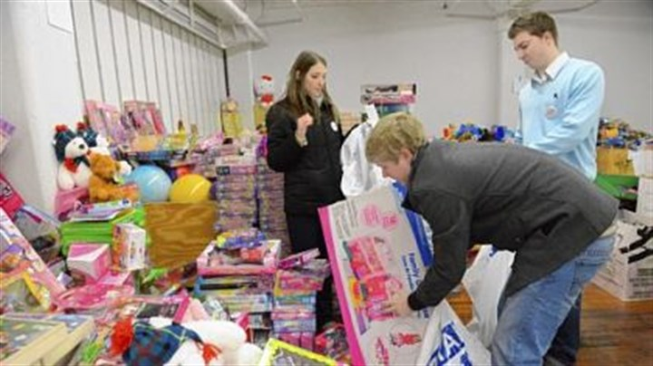 toys Volunteers, from left, Jayna Walters, 26, of Dormont, Brendan Orient, 23, of Mt. Lebanon and Alex Dziamniski, 23, of Whitehall sort toys Friday at the Toys for Tots open house in the Strip District.