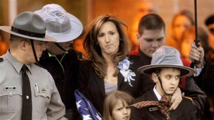 Trooper Richey's family Carrie Cornell, widow of Pennsylvania State Trooper Paul. G. Richey, and her children Conner, 9, and Catherine, 6, leave yesterday's funeral at Franklin Area High School.