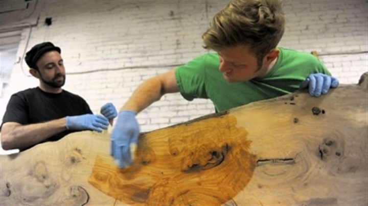 Urban Tree woodworking Apprentice Brian McLeod, left, works with Jason Boone to apply tung oil to a 12-foot shelf made from pin oak at Urban Tree.