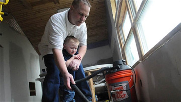 Vacuuming stink bugs Dean Osterritter, 33, of Spring Hill vaccums dead stink bugs in his attic with his son Dean Jr., 2.