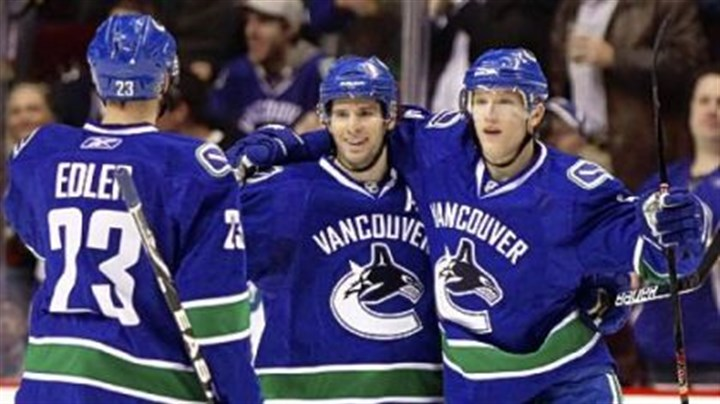 "Vancouver Canuck Ryan Kesler, center Vancouver Canuck Ryan Kesler, center, celebrates his goal with teammates Alexander Edler, left, and Christian Ehrhoff during a March game. Kesler is the cover athlete of the video game ""NHL 2K11,"" due out next week."
