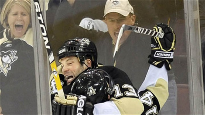 Very happy Bill Guerin gets a hearty hug from teammate Chris Kunitz after scoring the winning goal.