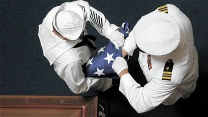 Veterans-1 Boatswain Mate 1 Raymond Monath, left, and Lt. Cmdr. Jeffrey Hawn fold an American flag for presentation to the family at the funeral of Navy veteran James Simmons Sr. at Forest Lawn Gardens Cemetery in Peters earlier this month.