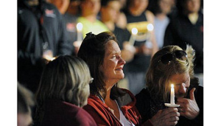 Vigil 1 Denise McNerney, mother of slain Washington & Jefferson football player Tim McNerney, holds a candle at a vigil in front of members of the football team.