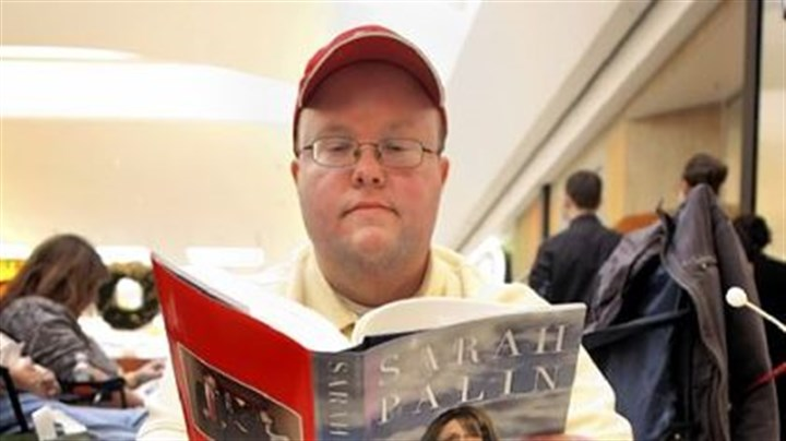 "Waiting for Palin Jeremy Hahn of Traverse City, Mich., reads as he and others wait in line yesterday for the signing of former Alaska Gov. Sarah Palin's new book, ""Going Rogue,"" at a Barnes & Noble bookstore in Grand Rapids, the first stop of her book signing tour."