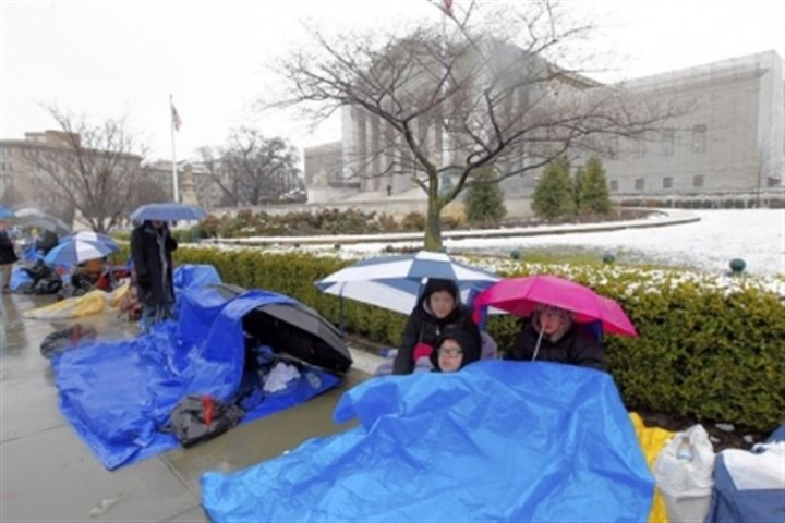 Washington, D.C., Taylor, Talla and Vincent Carter cover themselves from the snow Monday as they wait outside of the Supreme Court in Washington, D.C., to watch today's same-sex marriage hearing before the justices.
