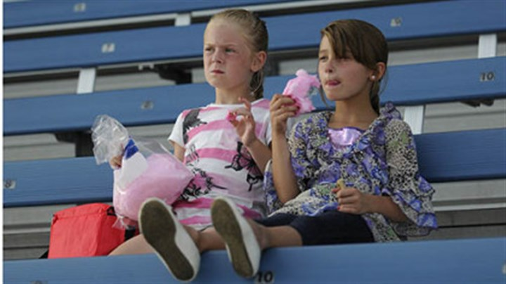 Washington Wild Things Twins Katie and Karlie Leadingham, 6, of Canonsburg eat cotton candy Saturday as they wait for the start of the Washington Wild Things game against the Traverse City Beach Bums.