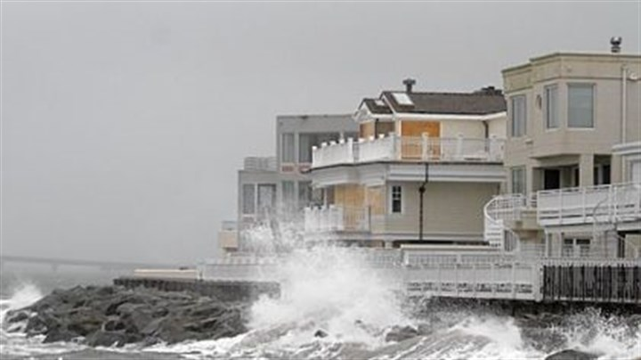 Waves crash Waves crash onto the sea wall protecting homes in Longport, N.J., Sunday.