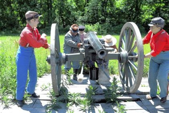 Women on the wheels Members of Carpenter's Battery, a Confederate gun crew, roll a cannon into place at a June re-enactment at Old Bedford Village. On the wheels are Yvonne Shuppe of Saltsburg and Cathy Griffey of Moon.