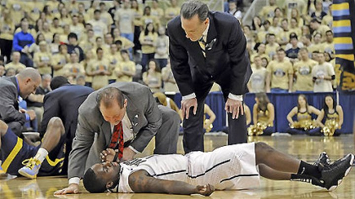 WoodallConcussion.jpg Pitt's Tray Woodall is attended to by trainer Tony Salesi and head coach Jamie Dixon after colliding with Marquette's Derrick Wilson in the first half of Marquette's win at the Petersen Events Center. Woodall left the game with a concussion.