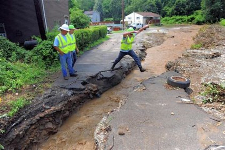 workers jump over gap Pennsylvania-American Water Co. workers jump over a gap in Irwin Street created after heavy rain flooded and destroyed portions of Irwin and Cemetery streets in Elizabeth Borough on Wednesday.
