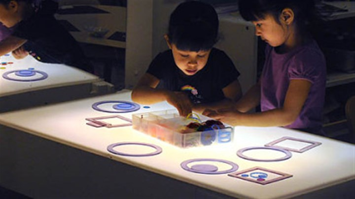 Working on a light table Four-year-old twins Uma and Jayanthi Simhan work on a light table with different shapes at Shady Lane School in Point Breeze.