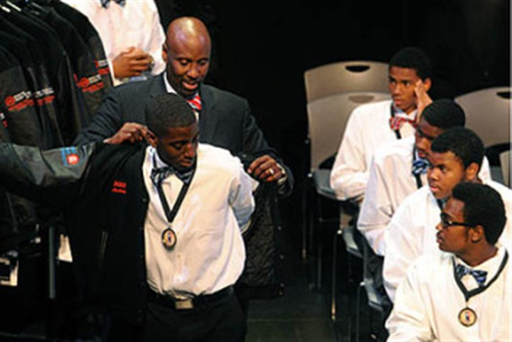 leadership Rex Crawley, co-director of the Black Male Leadership Development Institute, helps Justin Barnes put on a jacket at the August Wilson Center, Downtown, in 2012.