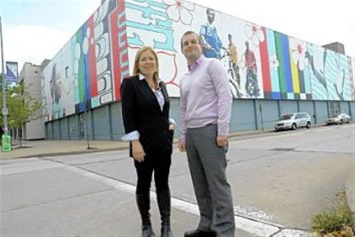 "Sprout Fund Sprout Fund founders Cathy Lewis Long and Matt Hannigan stand in front of the East Liberty mural ""Lend Me Your Ears,"" by Jordan Monahan."