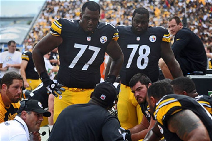 Tomlin talks to the line Steelers head coach Mike Tomlin, center, talks to tackles Marcus Gilbert (#77) and Guy Whimper (#78) during the second quarter of their 16-9 home game loss to the Tennessee Titans.