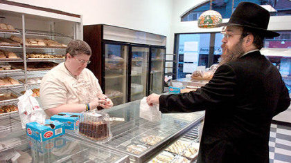 A regular Pat Griser, of North Braddock, waits on Rabbi Yossi Rosenblum, a regular customer from Squirrel Hill, at the Simple Treat Bakery on Murray Avenue.