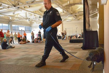 Coal and Don Brucker Coal, the accelerant detection dog with the Allegheny County Fire Marshal's office, parks himself at the training disc with accelerant as he's led on an exercise by Deputy Chief Fire Marshal Don Brucker at the Heinz History Center's event featuring working, service and therapy dogs