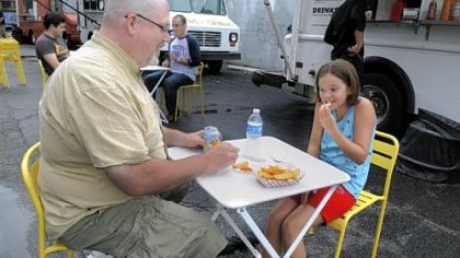 Dave Holcomb and his daughter Hadley Dave Holcomb and his daughter Hadley, 10, of Ben Avon, enjoy dogs from Franktuary's truck.