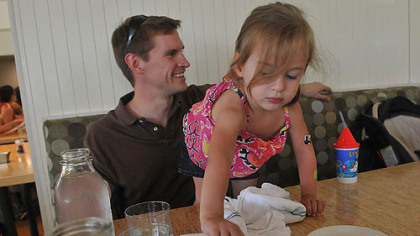 Dr. Karl Bowman and Emma Dr. Karl Bowman talks to his wife Melissa as their daughter Emma, 2, reaches for a sweetener packet during lunch at The Porch in Schenley Park.