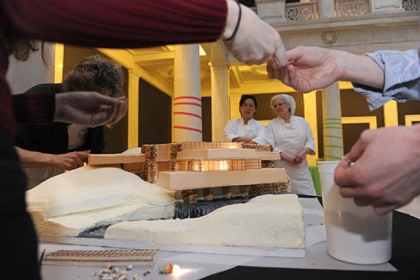 "'Fallingwater' Seung Mee Choi, assistant pastry chef, left, and Alice Leich, executive pastry chef, both of Parkhurst Dining at the Carnegie Museums, watch as the Loysen Kreuthmeier Architects/Prantl's Bakery team builds ""Fallingwater"" an edible cake."