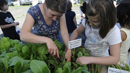 Farm markets Farmer Gillian Goldberg, left, helps Zoe Moran, 11, of Arlington, pick out a Swiss chard plant at the Who Cooks for You Farm stand on the opening day of the CitiParks Farmers' Market in East Liberty.
