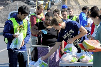 Food distribution Volunteers Shaun Gohel, left, 17, and Henry Mihm, 15, distribute food to Corletta Avant, 55, of North Braddock at a Produce to People event in Braddock.