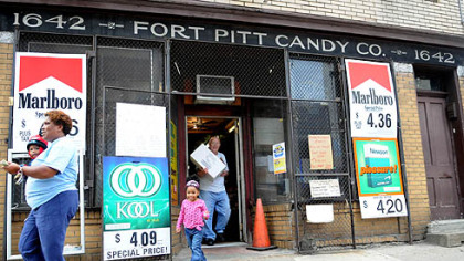 Fort Pitt Candy Bill McCoy of McKeesport, carries an order to the car for Zena Stafford, Allentown (with granddaughter, Zena, 2, in tow) at the Fort Pitt Candy Company in the Strip.