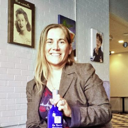 "Josephine Oria Josephine Oria, holding a bottle of ""La Dorita"" dulce de leche cream liqueur, in the company's new offices in Sharpsburg. In the upper left is a portrait of Maria Dora Germain, Ms. Oria's grandmother, who lives in Argentina and whose visage adorns the bottle."