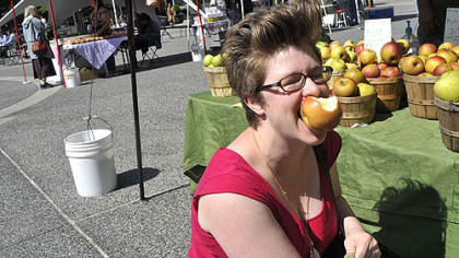 Morning Dew Orchards at Market Square farmers market Amanda Lowe of Lawrenceville reaches for her wallet to pay for an apple from Morning Dew Orchards at the farmers market in Market Square. The Downtown market opened its season today.