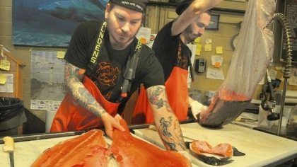 Penn Avenue Fish Co. Tim Reynolds, left, lays out a king salmon on a cutting board while Kyle Houghtelin unwraps sushi grade tuna Friday at Penn Avenue Fish Co. in the Strip District.