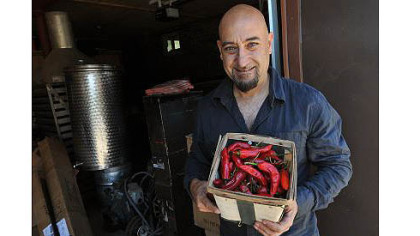 Peppers from the garden Nick DiCio of Reyna Foods displays a basket of chiles grown locally from Hatch seed.