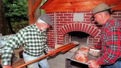 Ray Werner and his oven In 1998, Ray Werner, left, pulls bread from the oven that Mike Schafer, right, built for him.