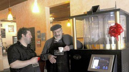 Rich Westerfield and John Casamassa Leaning on the store's new computerized coffee roaster, Aldo Coffee co-owner Rich Westerfield is with Aldo's head roaster, John Casamassa.