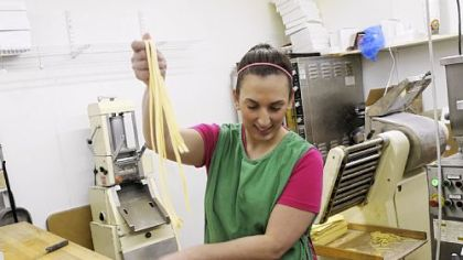 Sandy Falcione boxes fettucine After finishing rolling and cutting the pasta, Sandy Falcione boxes freshly made fettucine at Donatelli's Italian Foods.