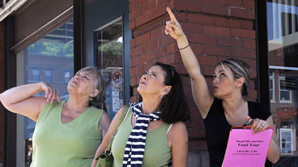 Viewing St. Stan's Sylvia McCoy-Emmenegger points out architectural details on St. Stanislas Kostka Church at 21st and Smallman streets to (from left) Bobbie Berg from Freedom Crossing and Tania Baker from Moon during the 'Burgh Bits and Bites Food Tour of the Strip District.