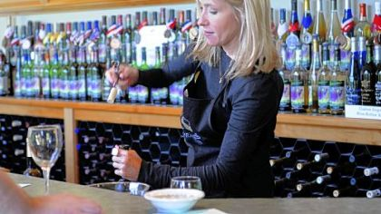 Winery at Sand Hill Hostess Cindy Molinaro opens a bottle at Greendance Winery.