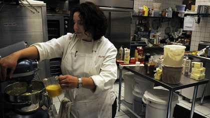 "Working the mixer Tammy Berkowitz adds eggs to her mixer for ""mocha cakes."""