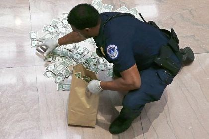 Capitol A U.S. Capitol police officer picks up money Thursday that was thrown on the floor inside the Hart Senate Office building in Washington, D.C., by activists protesting the government shutdown.