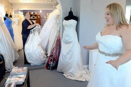 Koda Bridal Co-owner Mary Beth Ryfun, left, helps Medina Menozzi try on wedding gowns at Koda Bridal in Mt. Lebanon. Ms. Menozza says she plans to be early for the military brides gown giveaway.