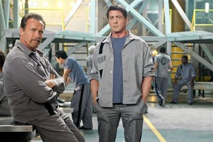 "'Escape Plan' Arnold Schwarzenegger, left, and Sylvester Stallone plot to get out of prison in ""Escape Plan."""
