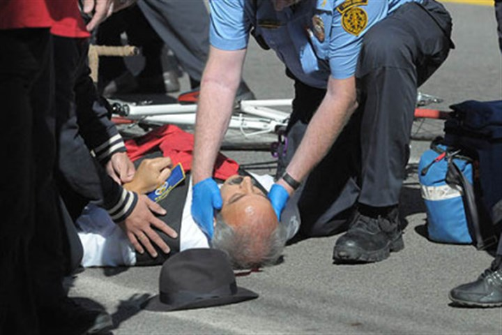 Run into At the Columbus Day Parade in Bloomfield, Giovanni Cimino of the Calabria Club is assisted by emergency personnel as he lies on the ground after being run into by a bicycle.