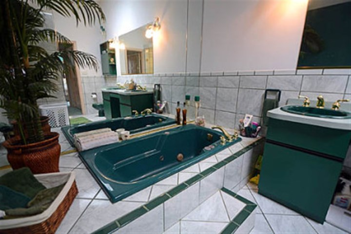The master bathroom Marble covers the floor and runs halfway up the walls, contrasting with deep emerald fixtures.