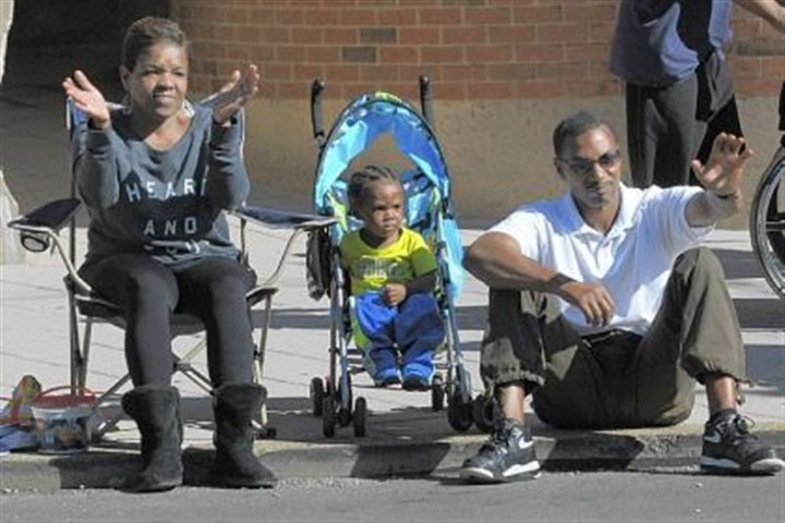 Watching Watching the Columbus Day parade in Bloomfield on Saturday are Jawanna and William Miller and their son Saahi, 17 months.