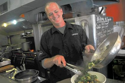 Dan Bartow Legends chef-owner Dan Bartow plates an order of beans and greens.