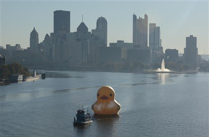 DuckyLeave10212013 The Rubber Duck, towed by an Alcosan boat, heads down the Ohio River, leaving Pittsburgh on the morning of Oct. 21, 2013.