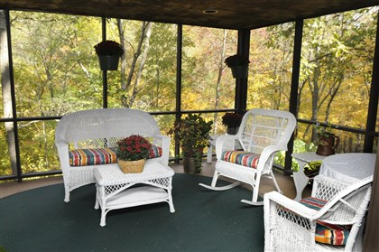 Back porch at Franklin Park The screened-in back porch offers a great view of the home' s private setting among the trees.